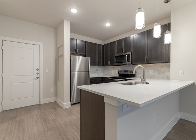Fully equipped kitchen with modern lights, kitchen island, and brushed nickel appliances