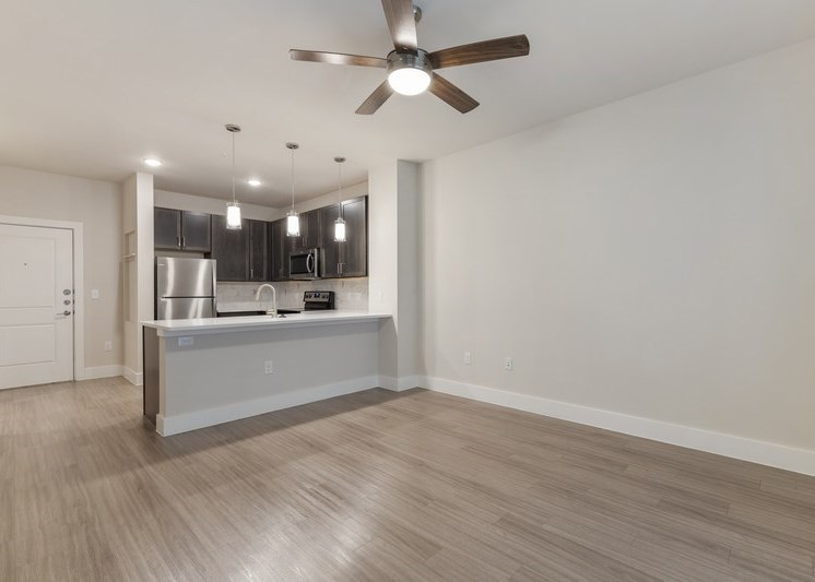 Living room with view of fully equipped kitchen, white painted walls, and ceiling fan