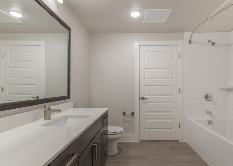 Bathroom with large vanity mirror, modern light fixtures, and large counterspace