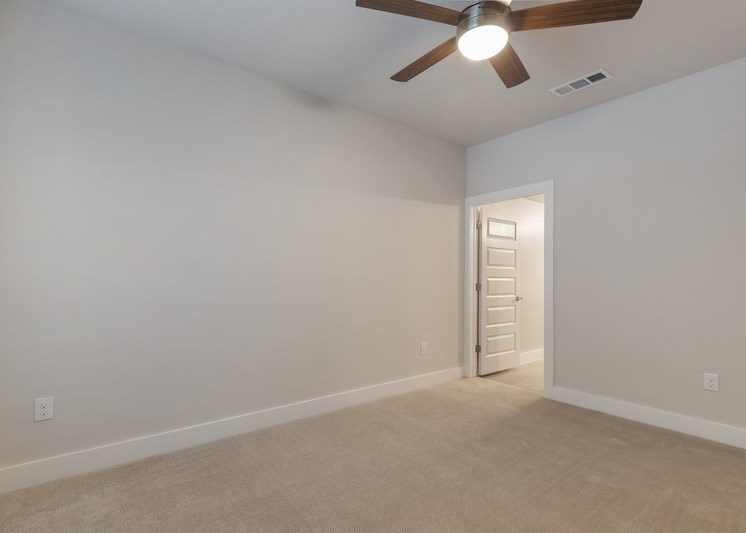 Bedroom with white walls, wall to wall carpet, and ceiling fan