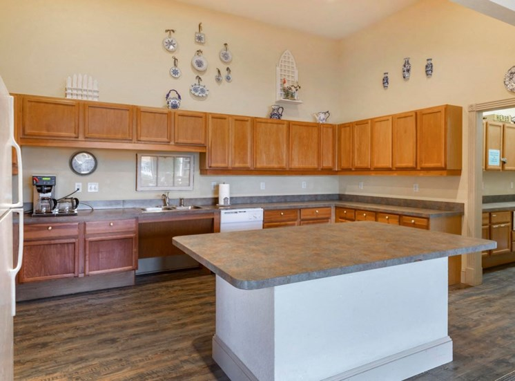 Clubhouse Kitchen with kitchen island, hardwood style floors, wooden cabinetry, and a white refrigerator