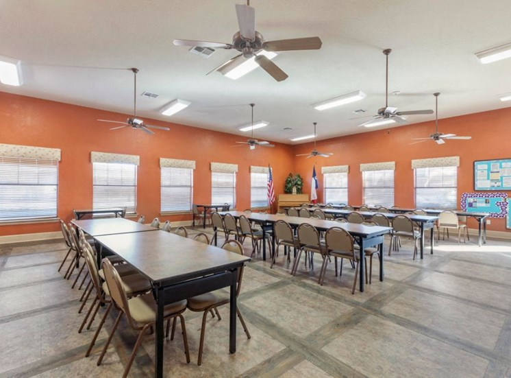 Clubhouse meeting room with tables, chairs, and orange walls
