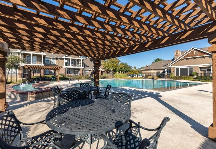 Swimming Pool with Tanning Deck, wooden pergola, and picnic tables and chairs