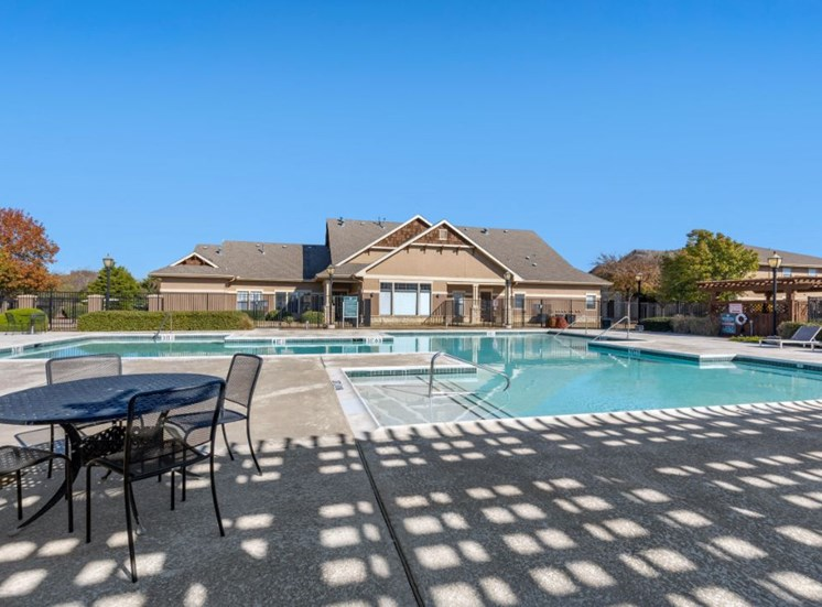 swimming pool with patio furniture and clubhouse exterior