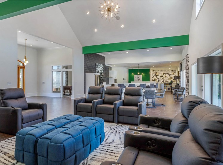 Clubhouse Lounge Area with Black Leather Armchairs Around Area Rug with Ottomans