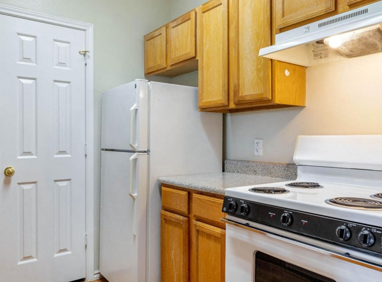 Fully Equipped Kitchen with Electric Stove and Tan Cabinetry