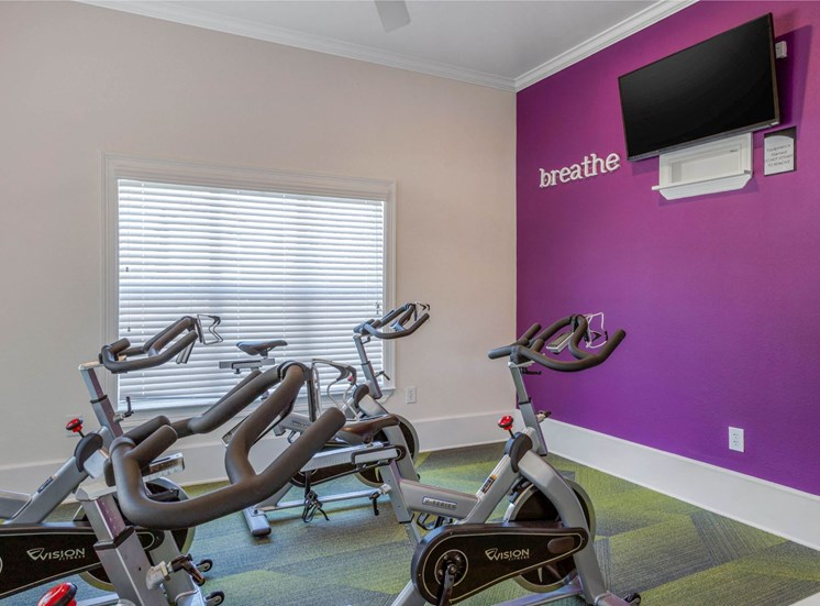 Fitness Center Cardio Equipment with Purple Accent Wall