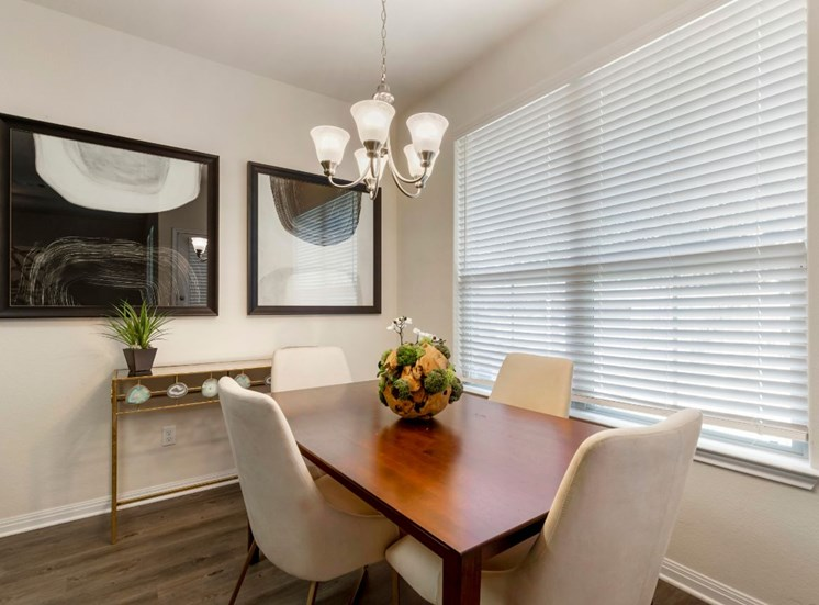 Dining room with a wooden table, two large framed photos,  window with blinds, and a decorative center piece.
