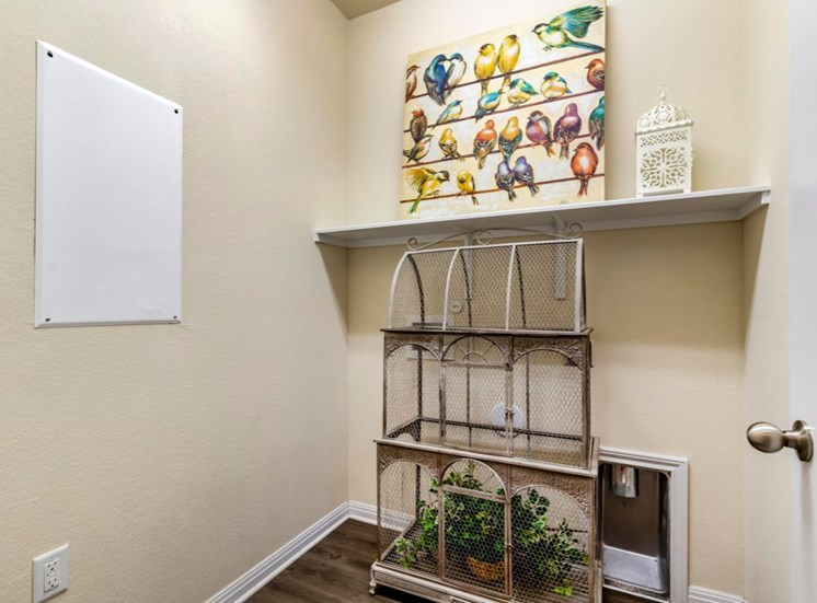 Decorated entryway with a portrait of colorful birds sitting on a shelf, a bird cage with a green plant inside, white trim, and hardwood style flooring
