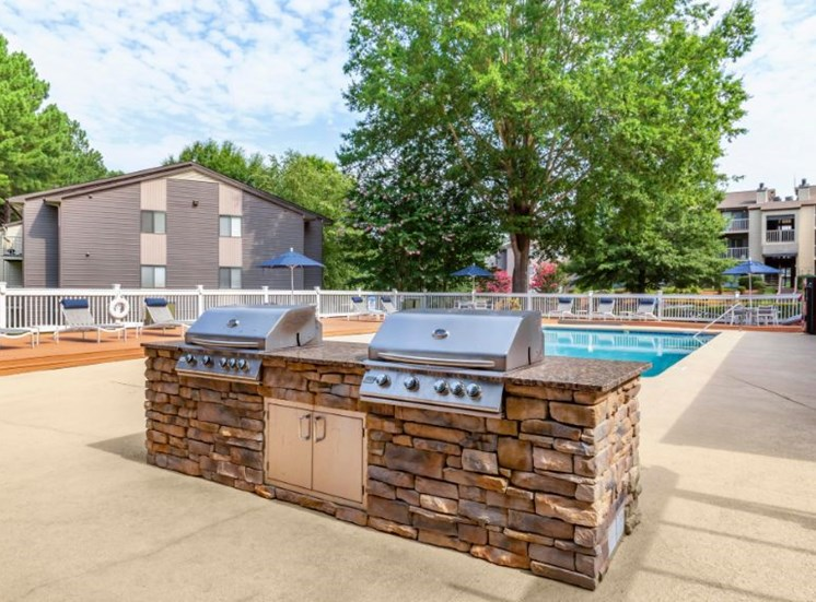 Summer Kitchen Grilling Station Next to Fenced in Pool with Trees and Building Exteriors in the Background