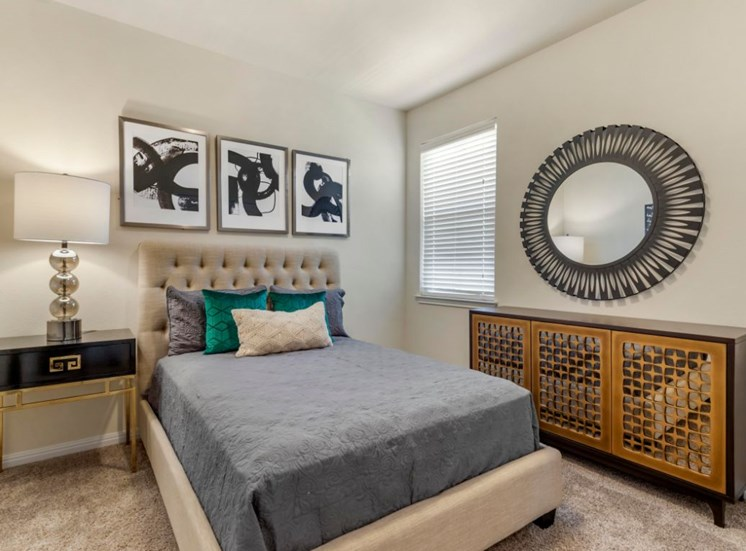 Decorated bedroom with a mirror on the wall, a full size bed with teal accent pillows, a night stand with a lamp, and three framed photos hanging on the wall