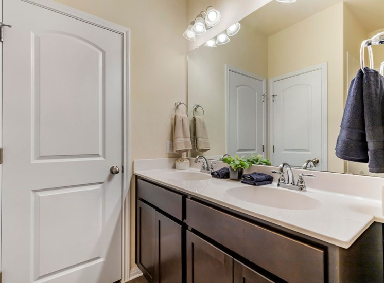 bathroom with vanity lights, blue and tan hand towels, large sink, and plenty of storage space under the counter