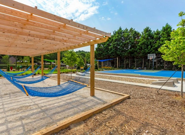 Pergola with Hammocks Next to  Blue Basketball Court Surrounded by Tall Trees