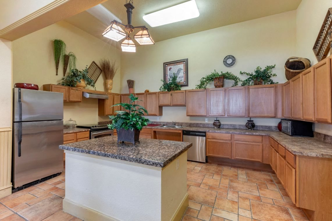 Clubhouse Kitchen with wooden cabinets, stainless steel appliances, and kitchen island