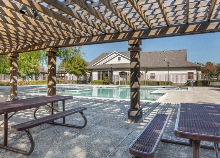 Swimming pool with wooden pergola, picnic tables, and tanning deck