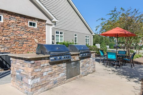 2 Poolside Grill Built into Bar with Picnic Table and Fenced in Pool in the Background
