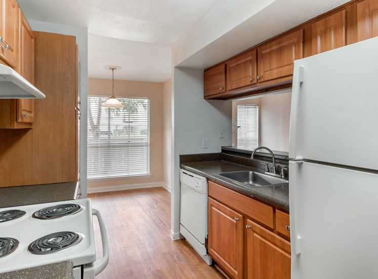 Fully equipped kitchen with white appliances and hardwood style flooring