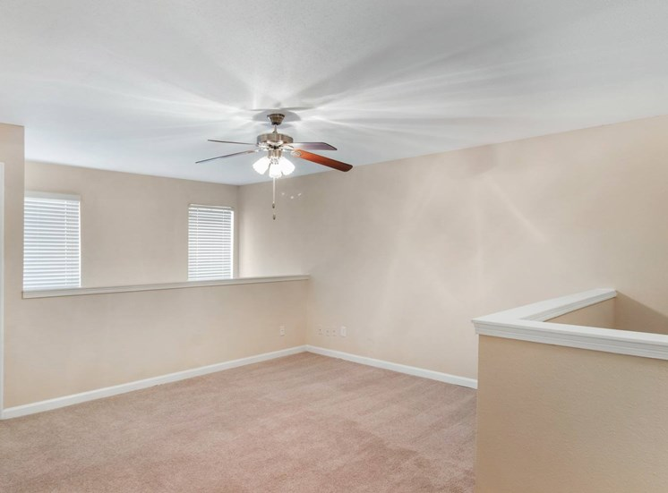 Living room with wall to wall carpet, ceiling fan, and white trim