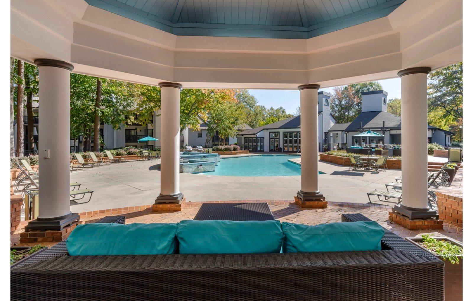resident lounge under a gazebo with white columns,  area overlooking swimming pool, turquoise and brown couch with brown whicker ottoman, lime green chaise lounge