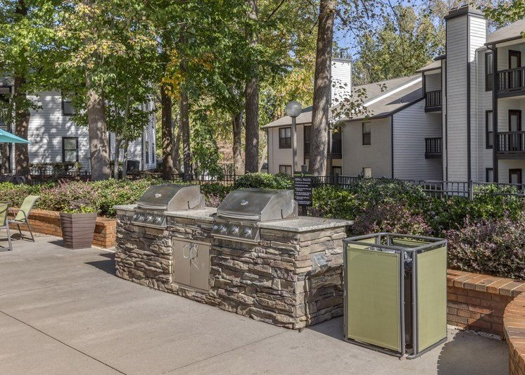 outdoor summer kitchen feature granite counter with two built-in, stainless steel gas grills, lime green pool furniture and lime green trash can. This area is surrounded by mature landscaping, and apartment buildings in the distance that overlook this area from the balcony