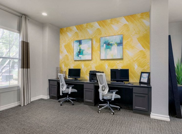 Business Center with Computers and a Printer on Grey Counter with Rolling Chairs Against Yellow Accent Wall