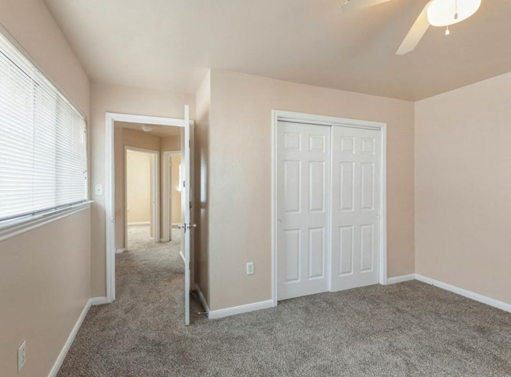 Bedroom with wall to wall carpet, ceiling fan, and closet with french doors