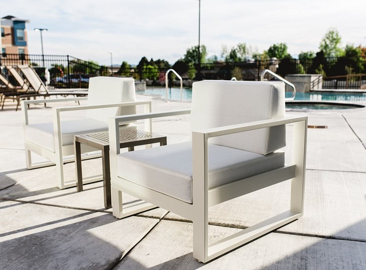 White Pool Armchairs on Sundeck Next to Swimming Pool