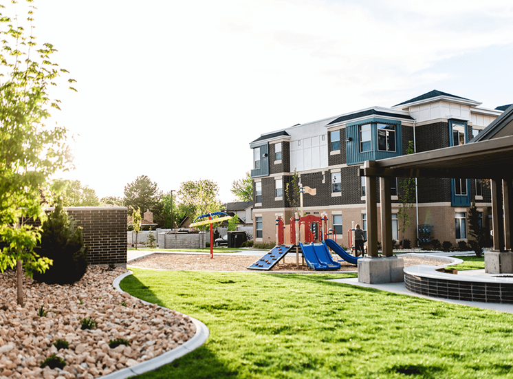 Courtyard Next to Pergola with Summer Kitchen with Firepit Next to Red, Blue and Yellow Playground