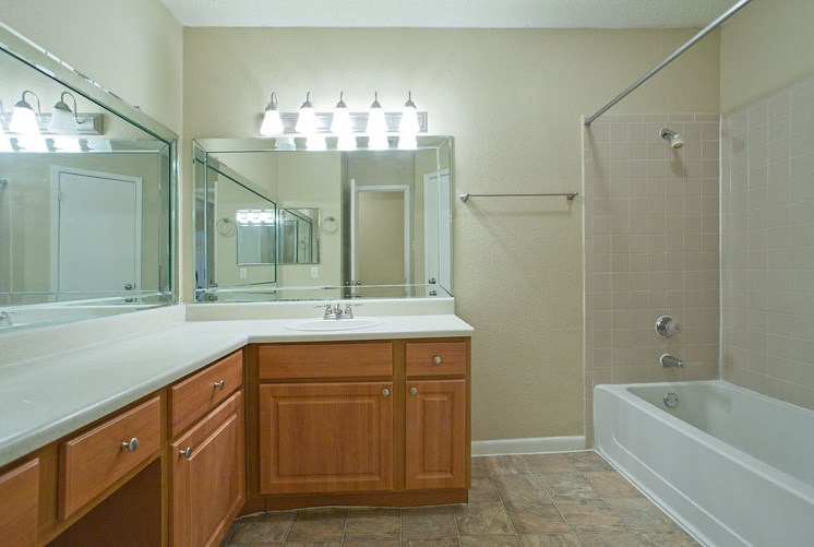 Bathroom with Large Vanity with White Counters Wood Cabinet Next to Bathtub with Shower
