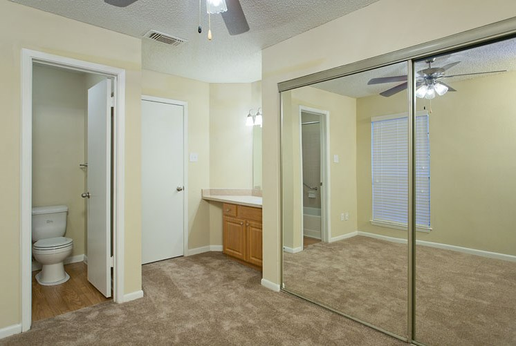 Open Layout Bedroom with Mirror Sliding Closet Doors Next to Vanity