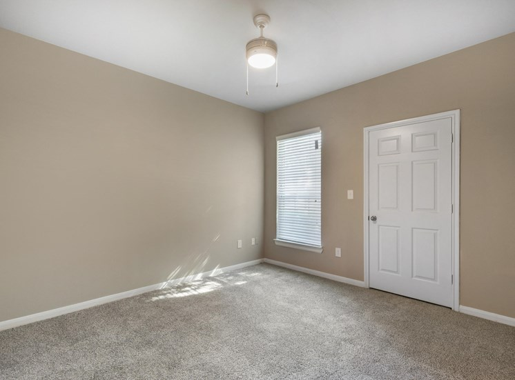 Living room with white door, window with blinds, wall to wall carpet, and tan walls