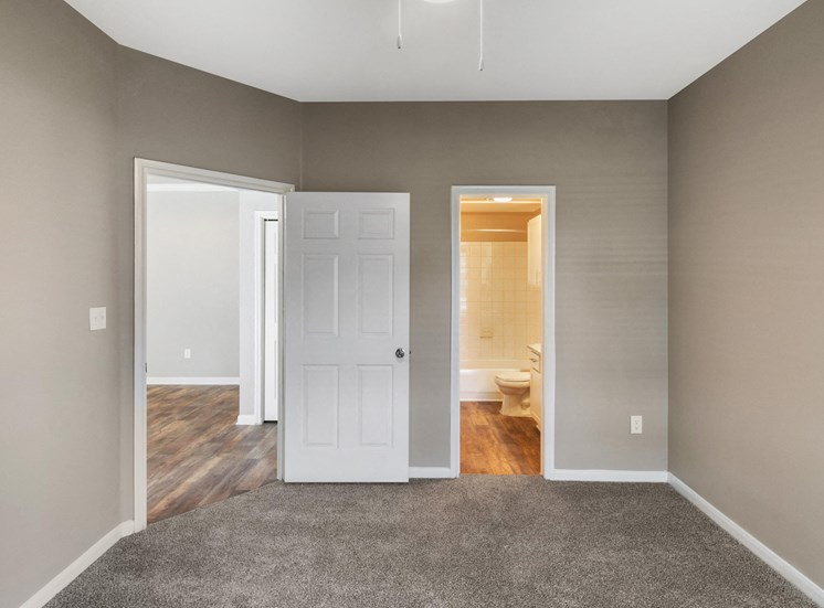 Bedroom with tan walls, white trim, en suite bathroom, and wall to wall carpet