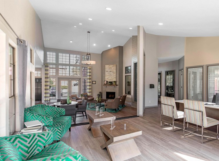 Clubhouse interior with hardwood style flooring, wooden furniture, natural light coming in from windows, and green/tan accent chairs