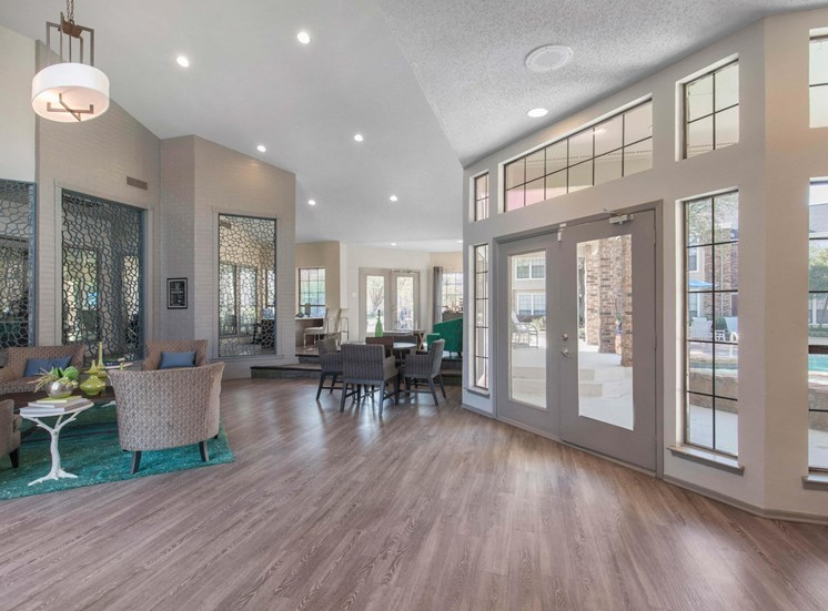 Clubhouse interior with hardwood style flooring, glass windows/doors, and a forest green accent rug