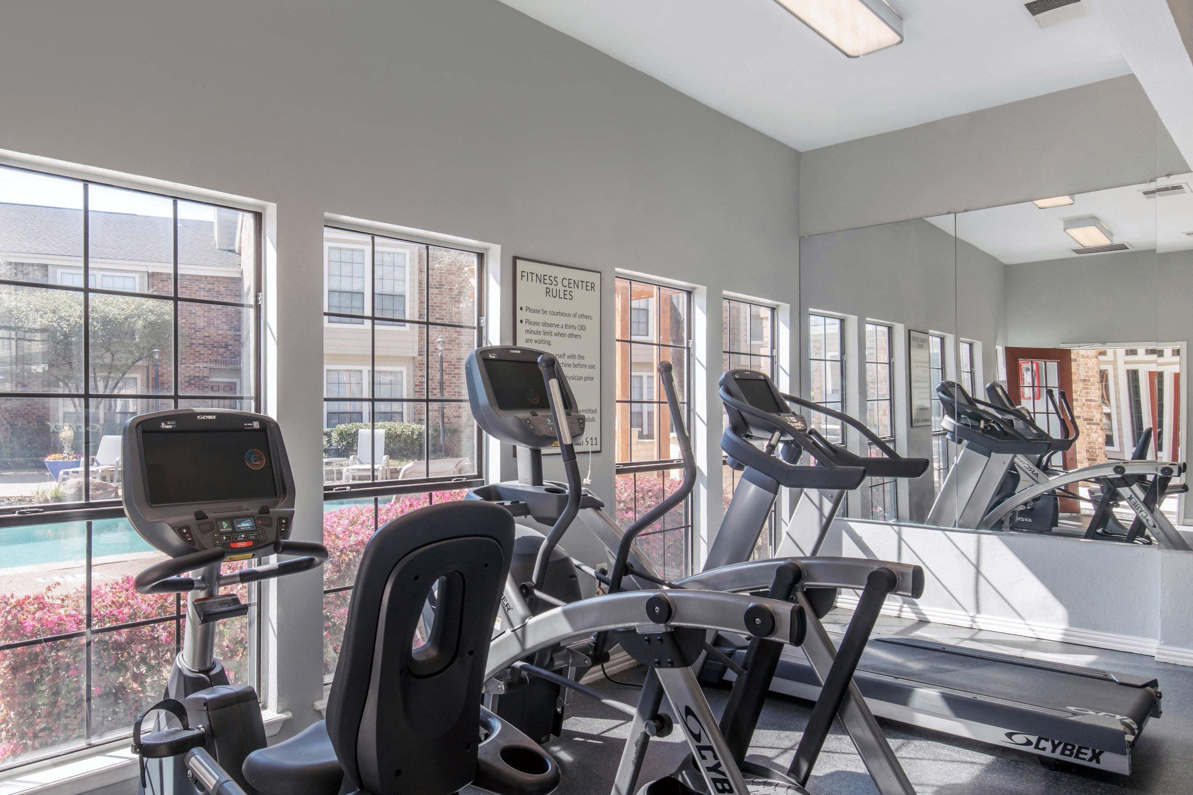 Fitness center with windows and view of pool with pink flowers/landscaping