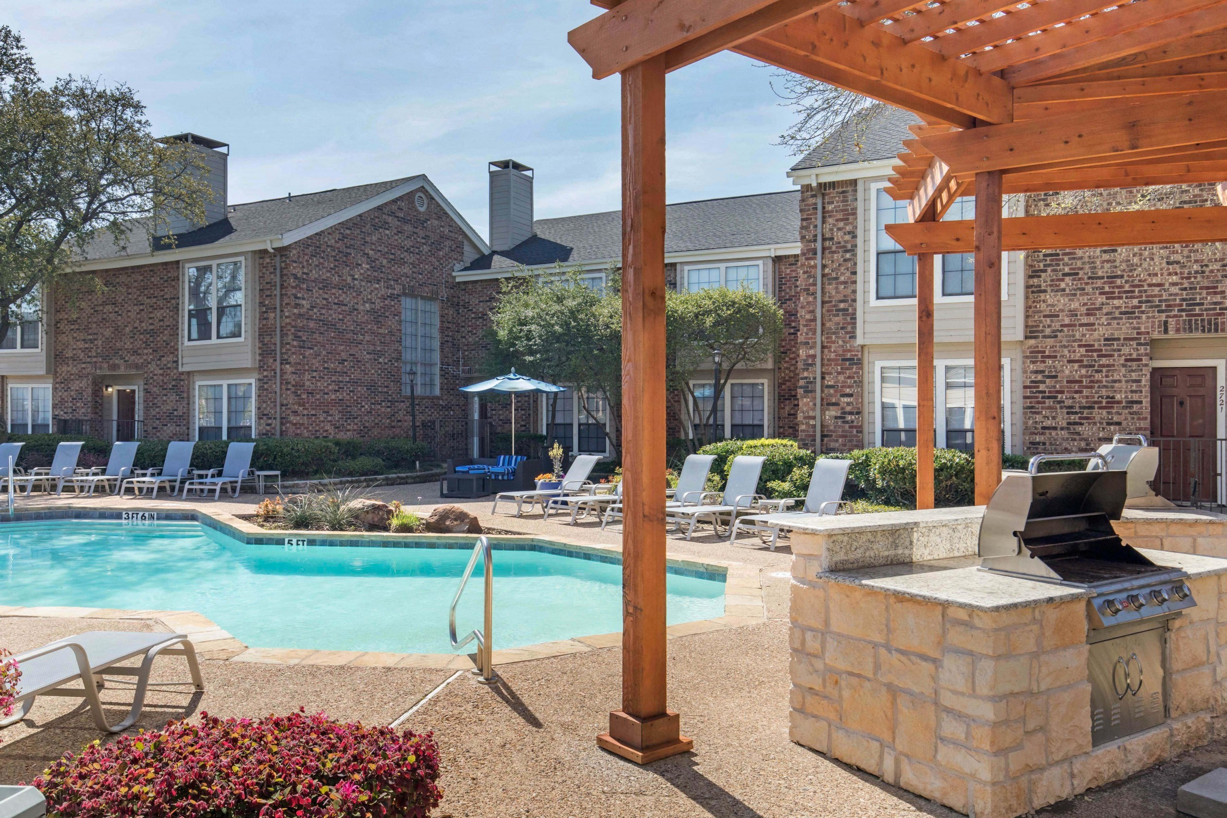 Sparkling blue swimming pool with wooden pergola and grilling station