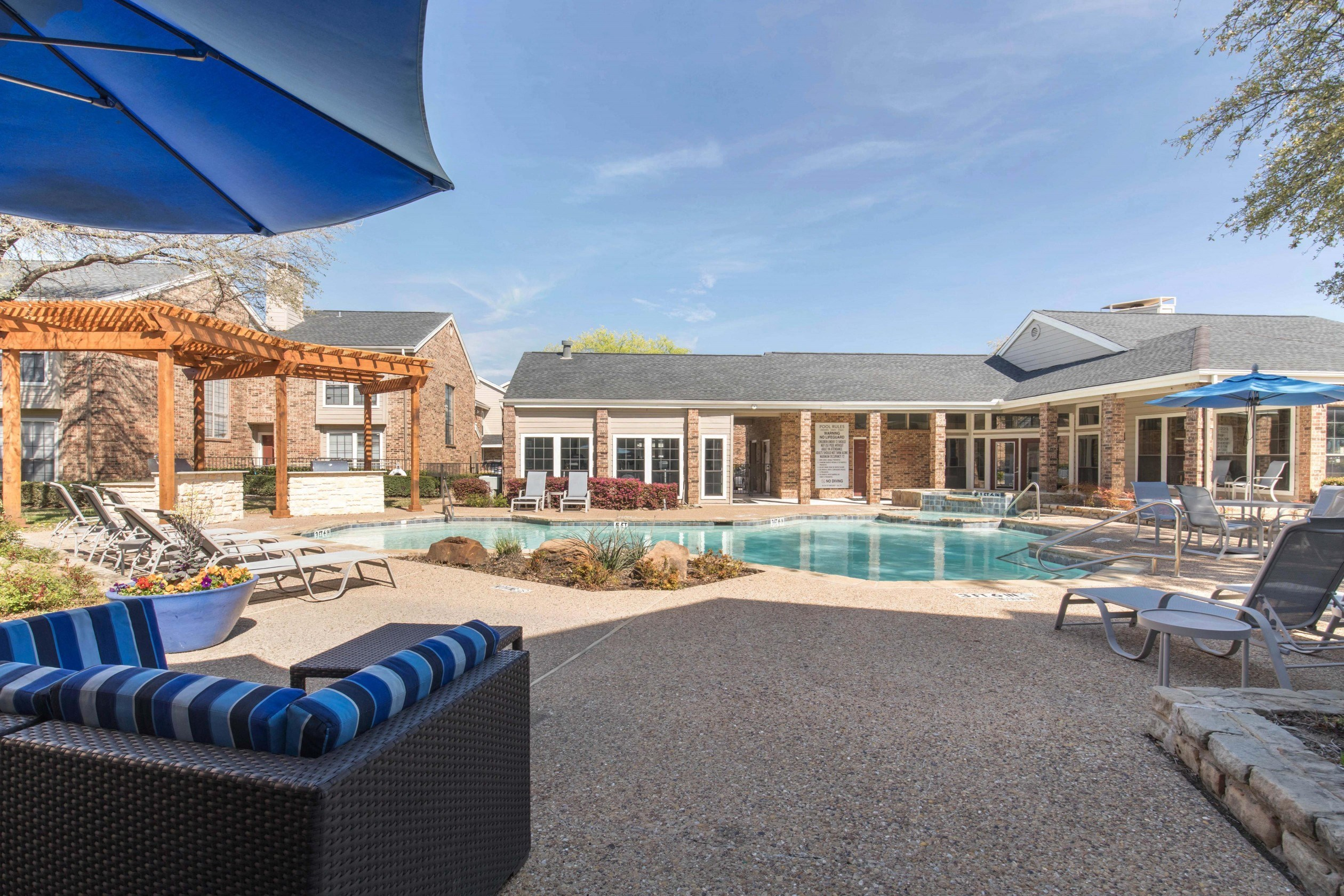 Sparkling blue swimming pool with spacious tanning deck, clubhouse exterior in the background, and blue and gray striped pool furniture