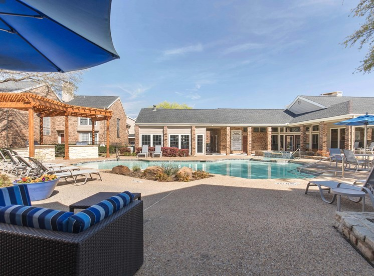 swimming pool with spacious tanning deck, clubhouse exterior in the background, and blue and gray striped pool furniture