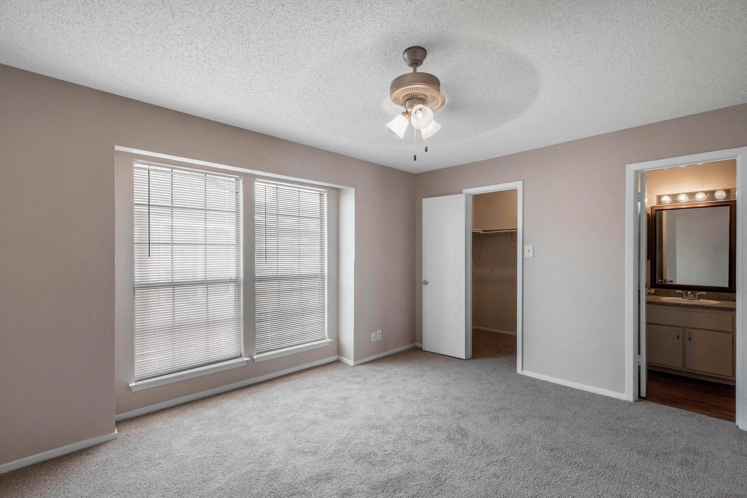 Wall to wall carpet, ceiling fan, en-suite bathroom,  spacious walk in closet, and blush colored walls