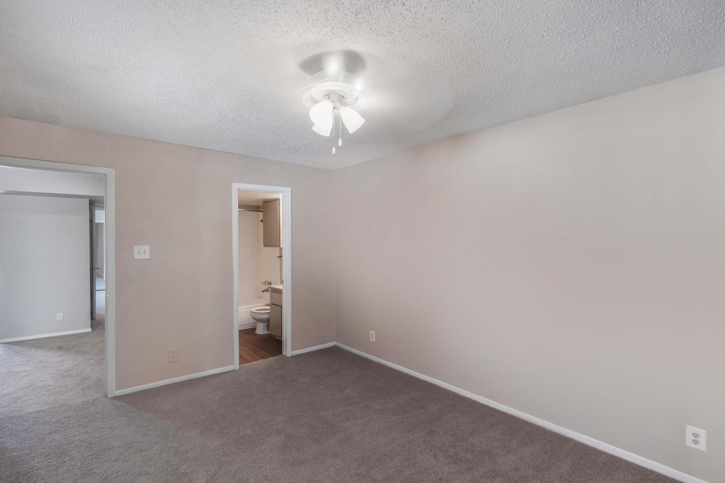 Bedroom with brown wall to wall carpet, ceiling fan, peach colored walls and an en-suite bathroom