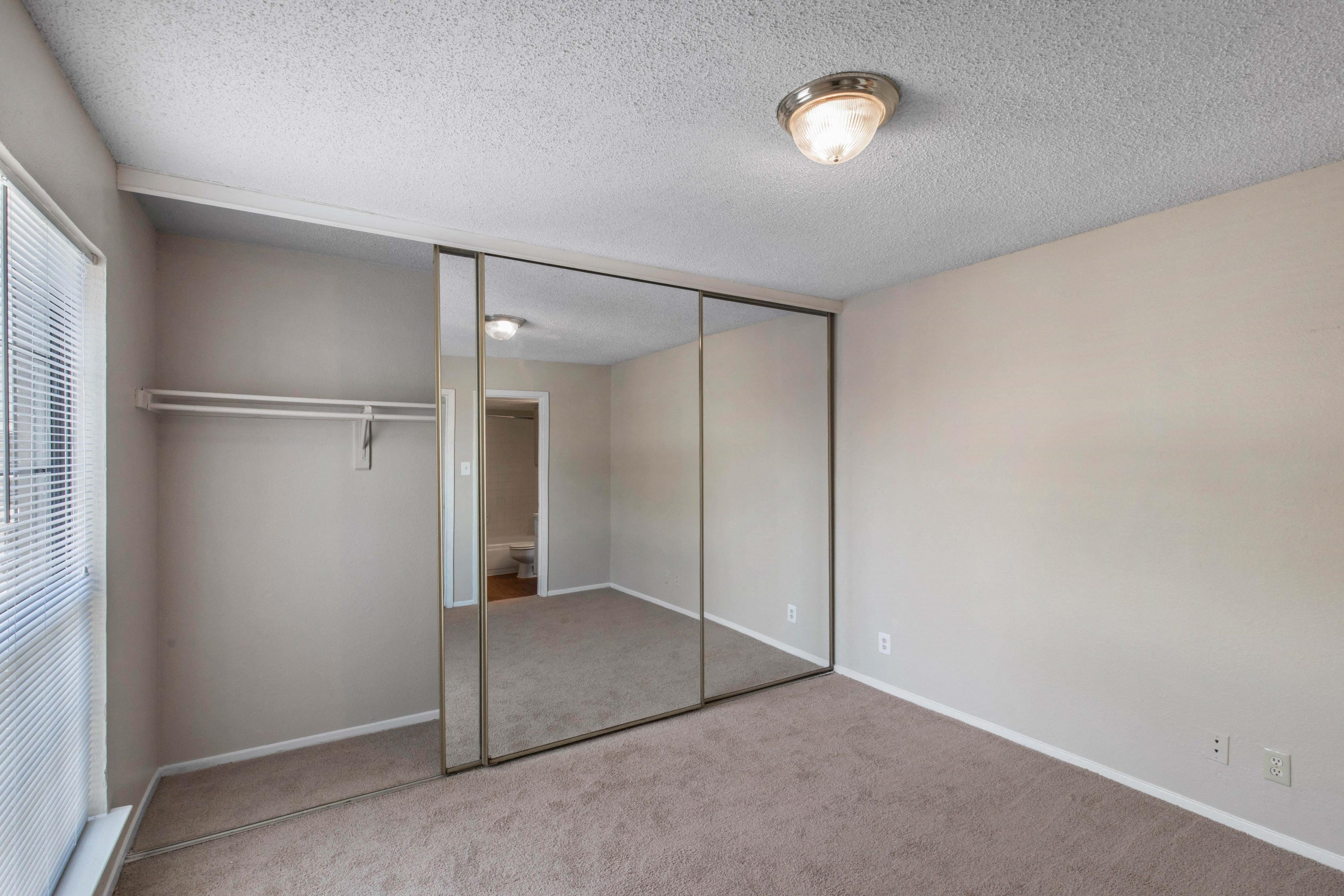 Bedroom with wall to wall carpet, eggshell white walls, bright white trim, bulb light, and mirrored closet doors