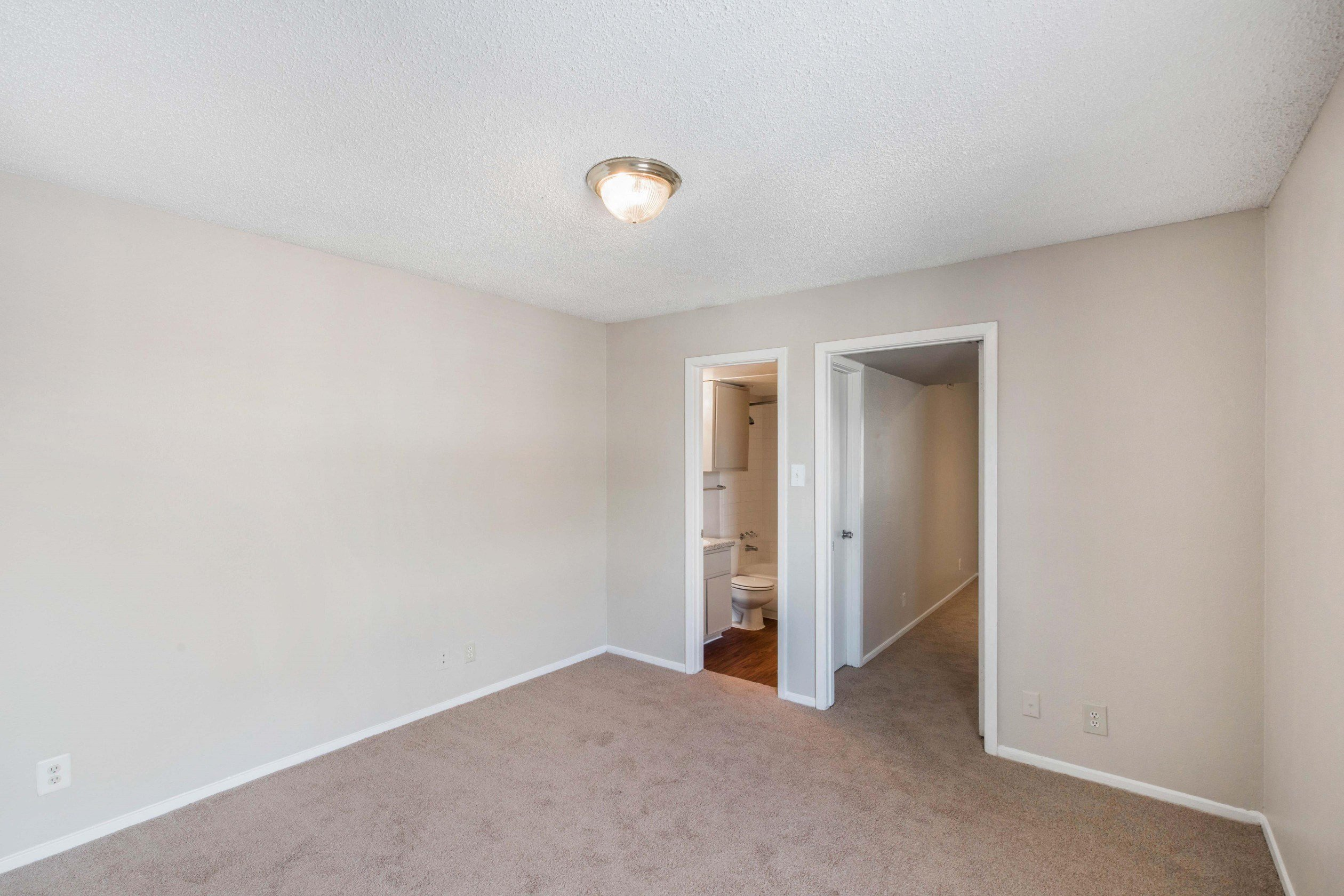 Bedroom with wall to wall carpet, eggshell white walls, white trim, and en-suite bathroom