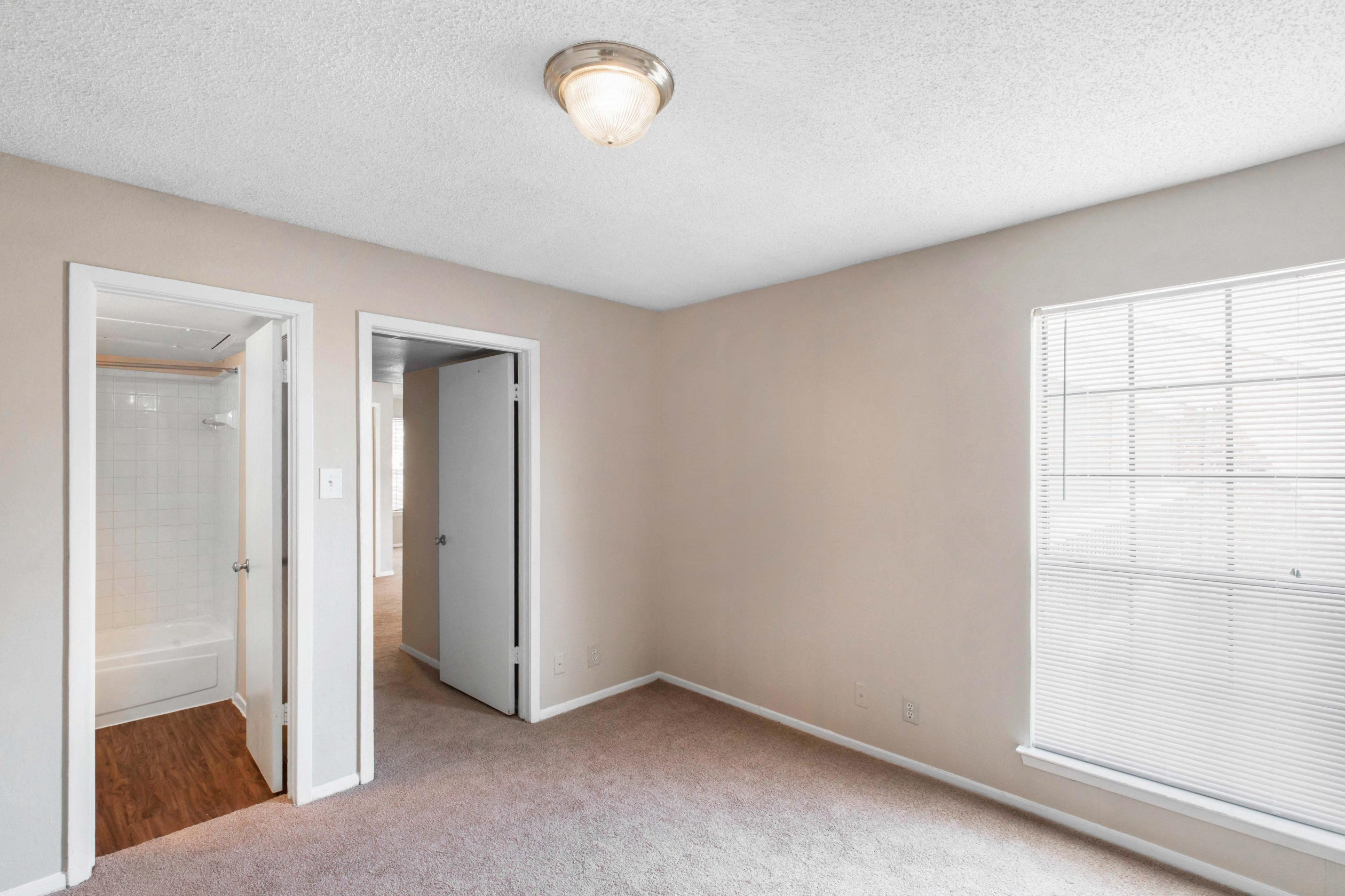 Bedroom with wall to wall carpet, spacious window with white blinds, and en-suit bathroom, with peach colored walls and white trim