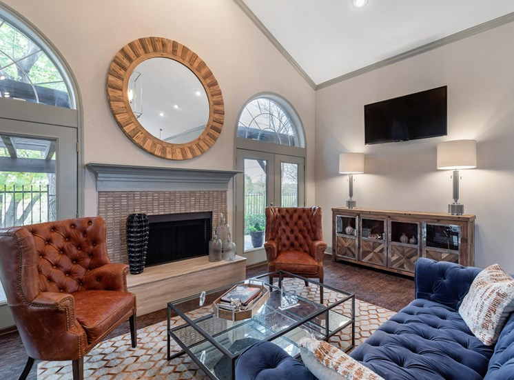 Clubhouse interior with hardwood style flooring, arched windows, a mounted television, and two accent chairs