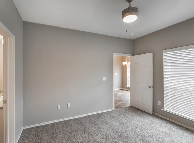 Bedroom with gray walls, white doors, white trim, and wall to wall carpet