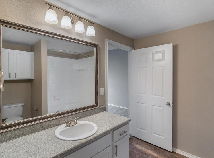 Bathroom with garden style bath tub, additional cabinet located above the toilet, and hardwood style flooring