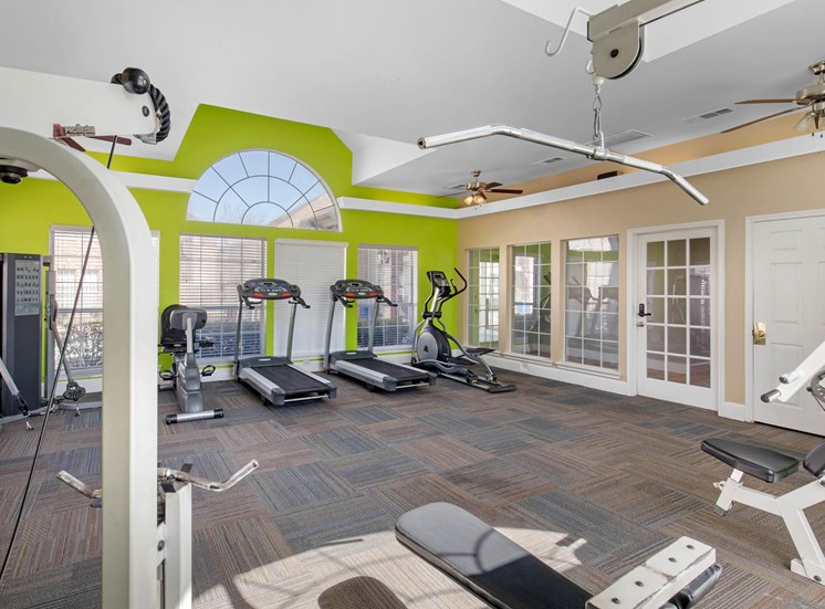 Fitness center with green accent wall, treadmills, ceilings fans, and large windows