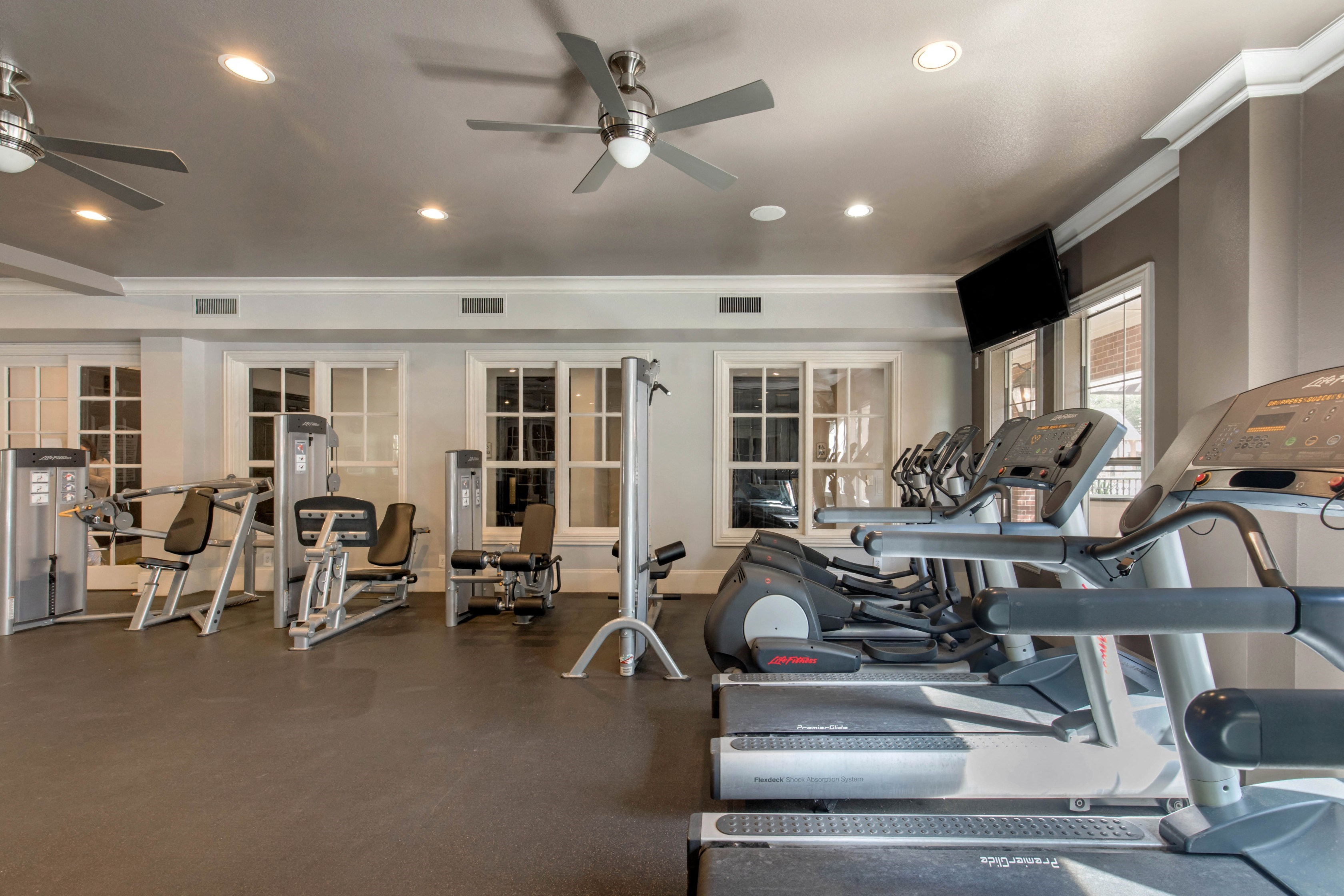 Fitness center with ceiling fans, treadmills, and a spacious area to workout