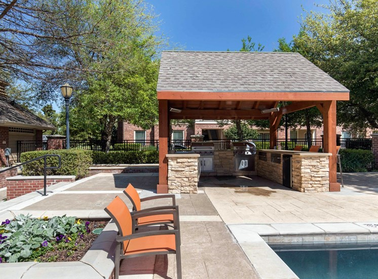 Swimming pool with tanning deck and orange lounge chairs grilling station under awning