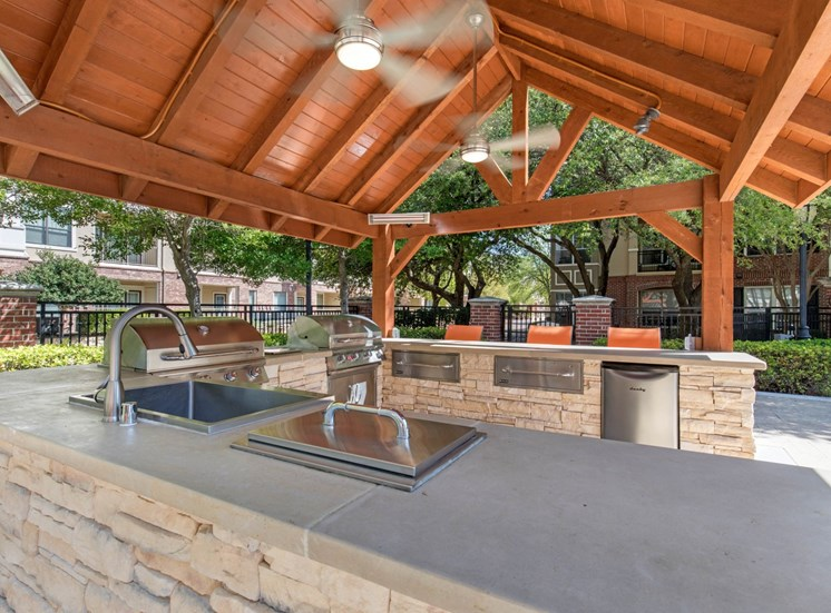 Outdoor kitchen with grilling station with awning and ceiling fans